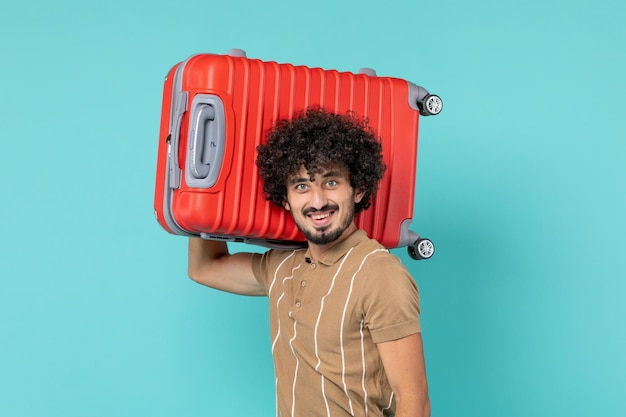 Man in vacation with big suitcase smiling on blue
