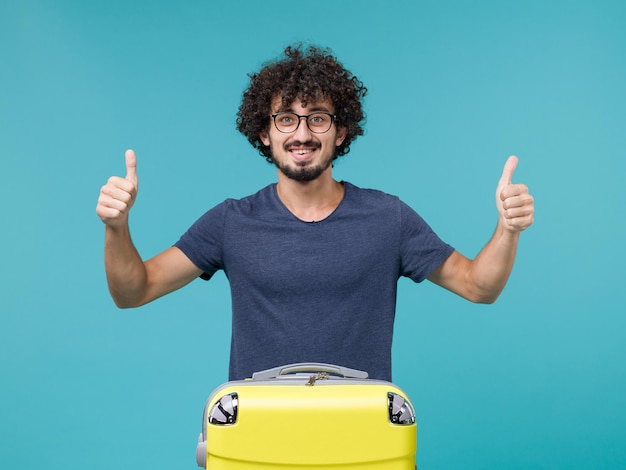 Man in vacation with big yellow suitcase feeling happy on blue