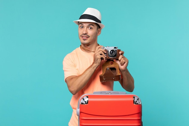 Man in vacation with his red suitcase and camera on blue