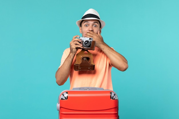 Man in vacation with his red suitcase and taking photos with camera on blue