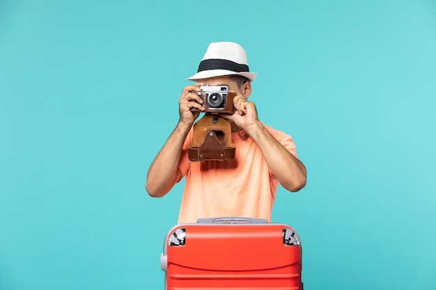 Man in vacation with his red suitcase taking photos with camera on blue