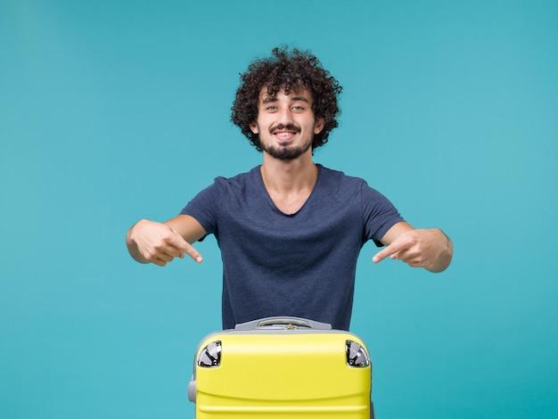 Uomo in vacanza con la sua valigia gialla su blue