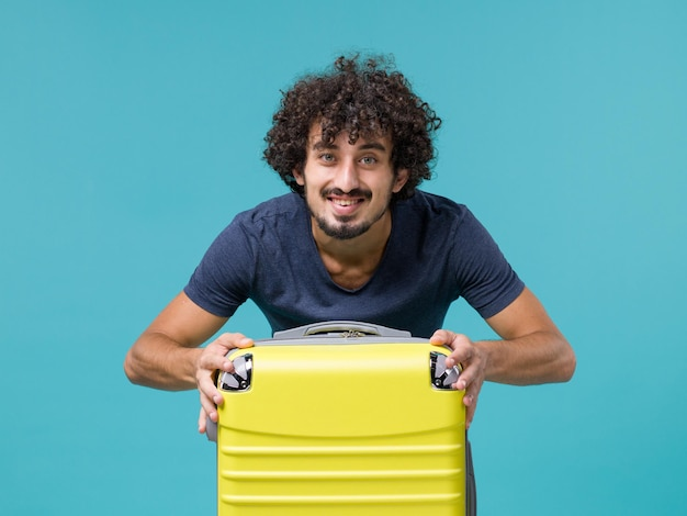 Man in vacation with his yellow suitcase smiling on blue
