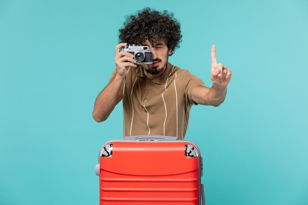 Man in vacation with red suitcase taking photos with camera on blue floor journey plane vacation sea voyage trip