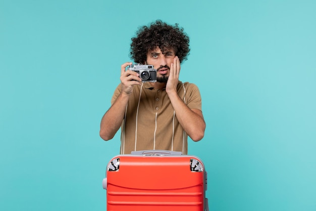 Man in vacation with red suitcase taking photos with camera on blue