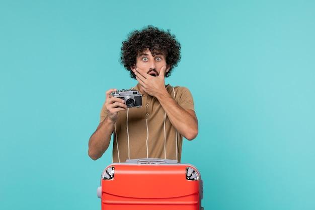 Uomo in vacanza con valigia rossa che scatta foto con la fotocamera su blue