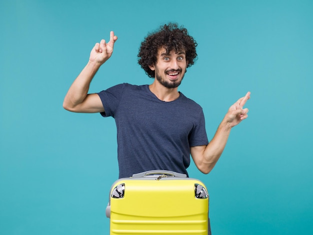 Man in vacation with yellow suitcase crossing his fingers on blue