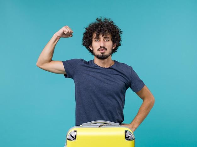 Uomo in vacanza con valigia gialla che si flette sul blu