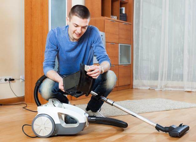 거실의 쪽모이 세공 마루 바닥에 진공 청소기로 진공 청소기로 청소하는 남자