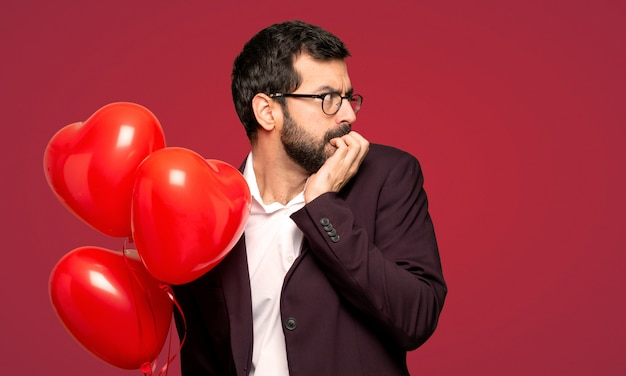 Man in valentine day is a little bit nervous and scared putting hands to mouth over red background