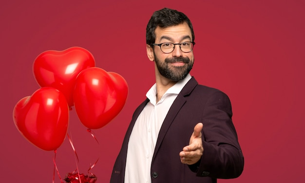 Man in valentine day shaking hands for closing a good deal over red background