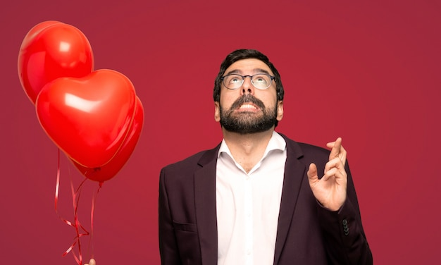 Man in valentine day with fingers crossing and wishing the best over red background