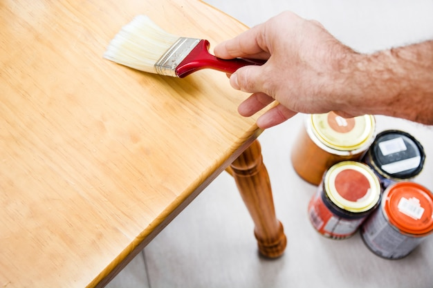 Man varnishing a chair with paintbrush