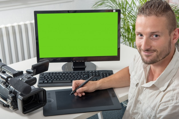Man video editor with graphic tablet and professional video camera, green screen
