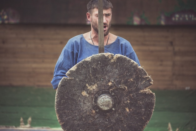 A man in a viking costume holds a sword and a shield