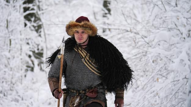 Человек викинг собирается в зимнем лесу