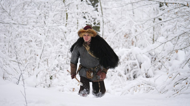 Man viking going in the winter forest.