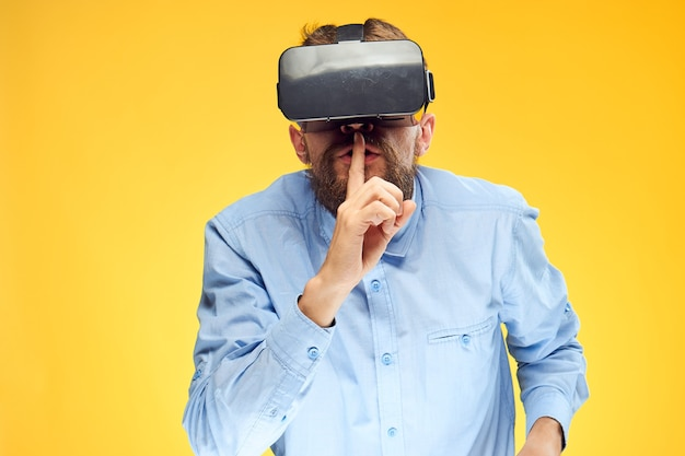 Man in virtual reality glasses with a finger on his mouth