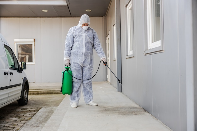 Man in virus protective suit and mask disinfecting buildings of coronavirus with the sprayer. infection prevention and control of epidemic. world pandemic.