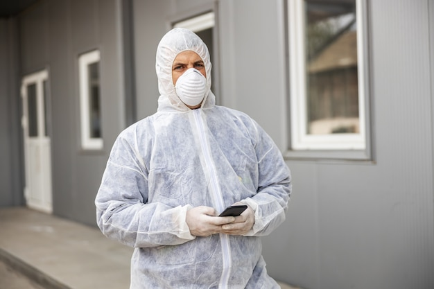 Man in virus protective suit and mask looking and typing on mobile phone smartphone, disinfecting buildings of coronavirus with the sprayer. epidemic. world pandemi