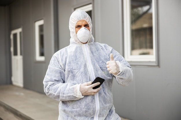 Man in virus protective suit and mask looking and typing on mobile phone smartphone, disinfecting buildings of coronavirus with the sprayer