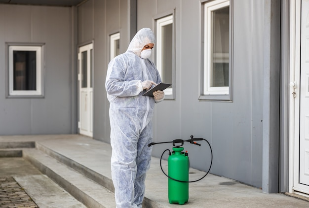 Man in virus protective suit and mask looking and typing on tablet, disinfecting buildings of coronavirus with the sprayer. epidemic.