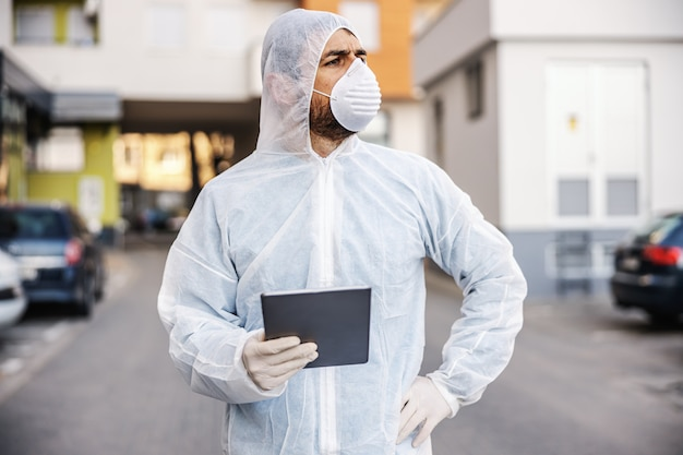 Man in virus protective suit and mask looking and typing on tablet, disinfecting buildings of covid-19 with the sprayer. infection prevention and control of epidemic. world pandemic.