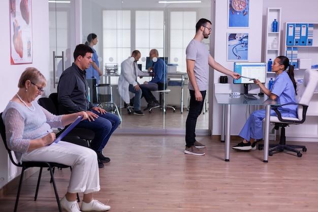 助手にレントゲン写真を与える医療チェックのために病院の診療所を訪れる男性