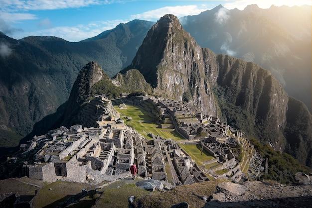 ペルーのアンデス山脈にあるマチュピチュのインカ遺跡の素晴らしいパノラマの景色を訪れる男