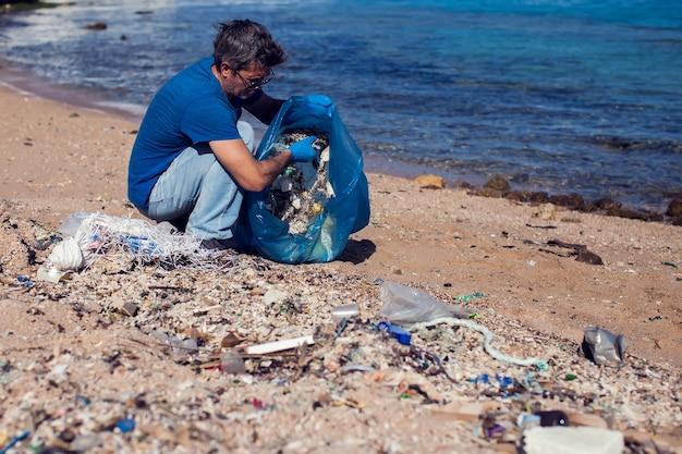 Человек-волонтер в синей футболке с большим мешком для сбора мусора на пляже. концепция загрязнения окружающей среды