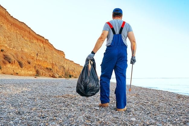 リーチエクステンダースティックでビーチでゴミを収集するユニフォーンの男性ボランティア