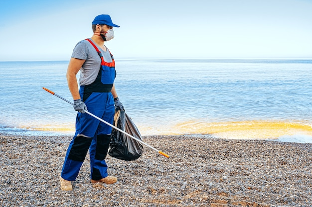 Man volunteer in uniforn collecting garbage on the beach with a reach extender stick