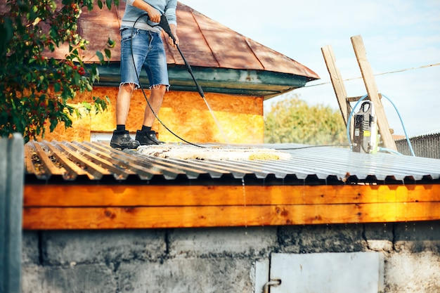 Man wach clean carpet outdoor on roof with water