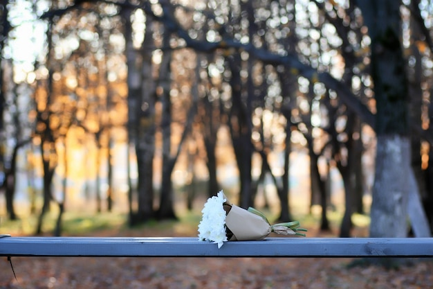 Man waiting on a bench the date in autumn park with flower