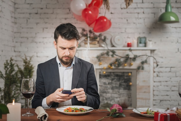 Man waiting for date checking phone