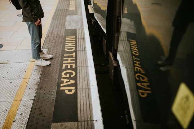 プラットフォームで電車を待っている男