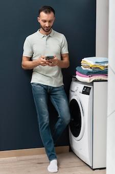 洗濯機がプログラムを終了するのを待っている男