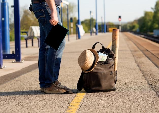 緑の旅行バックパックで電車を待っている人