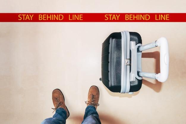Человек ждет на земле знак в аэропорту с черным чемоданом