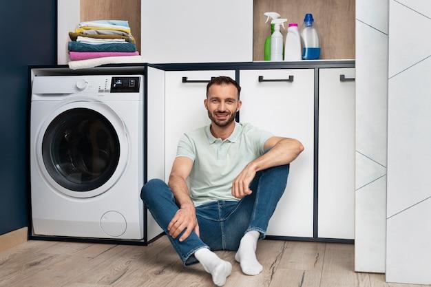 Man waiting for the washing machine to finish its program