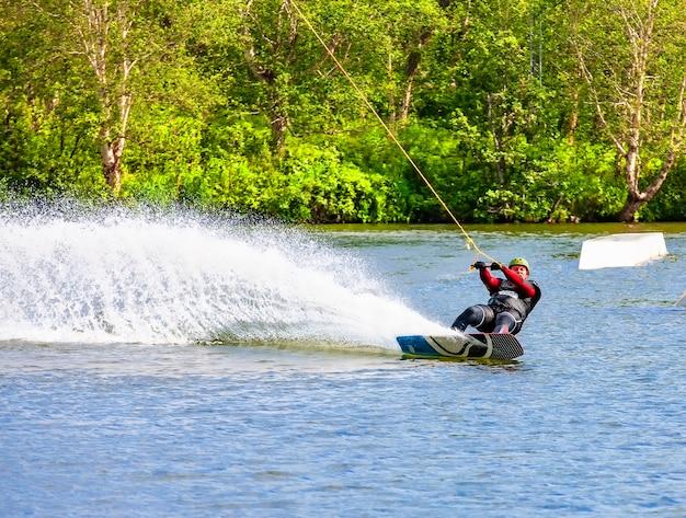 ボートの後ろのカムチャツカの湖でウェイクボードする男