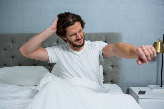 Man waking up in bed and stretching her arms
