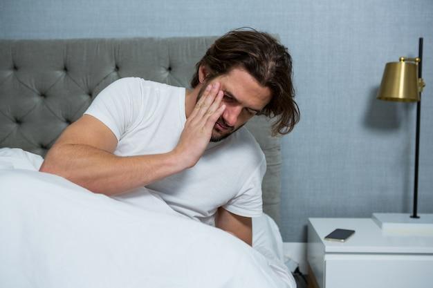 Человек просыпается от сна в спальне