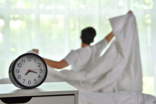 남자는 아침에 일어나 침대에 앉아서 스트레칭을 하고 알람 시계에 집중한다