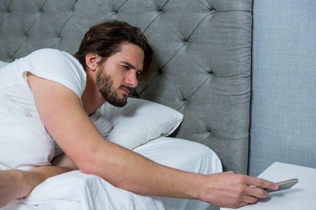 Человек просыпается с мобильным будильником