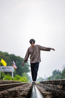 男は暖かい光で鉄道を歩き去ります。セレクティブフォーカス。