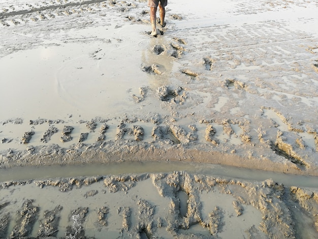 Man walk and lots foot print on dirty muddy ground