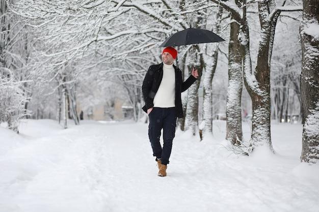 A man on a walk in the park. young man with an umbrella under the winter snowfall.