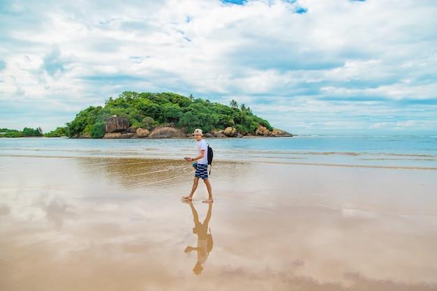 A man walking along the beach of sri lanka.