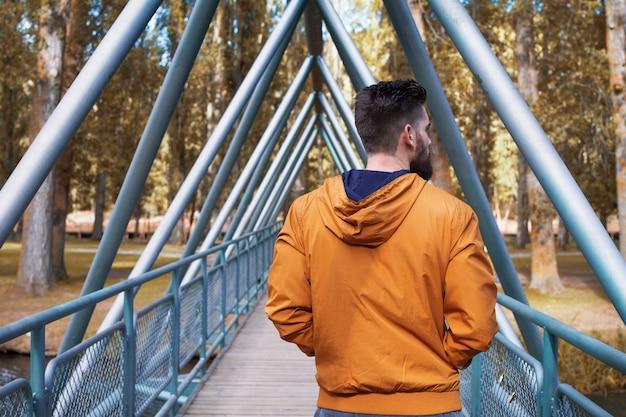 Man walking along the bridge that crosses the river.